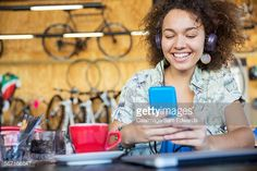 Stock Photo : Smiling woman with headphones texting on cell phone in bike shop