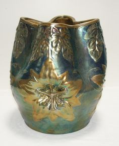 "Item # 258. A Zsolnay vase of exceptional glaze and décor. Metallic blue and silver Eosin glaze with very faint copper / lilac eosin hues over a form of lilies and leaves. Hand etched form # 5424 ( as opposed to an incised form number which made indicate a prototype design) and printed Zsolnay Factory mark.  Circa 1899. The clay body is very heavy. 10.5"" tall. Hand drawn circular factory mark. Excellent condition; no restoration. Minor stress lines on the underside. This vase weighs 10 lbs…"