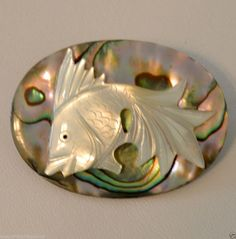"""realistic shaped fish button, carved from mother of pearl (MOP) or shell. The fish is set on a gorgeous oval shaped, very colorful abalone shell. The button is approximately 1-1/2"""" in length. SOLD $56.00"""