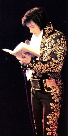 """Elvis on stage reading from the book written by John O'Grady. O'Grady was a private detective friend of Elvis who was involved in the Patricia Parker paternity suit. He is wearing his """"Black Spanish Flower"""" jumpsuit"""