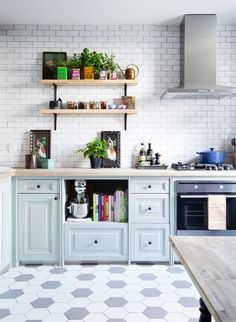Love the blue cabinets, subway tile back splash and the hexagon tile  floor.  Pale Blue Kitchen | photo Ashley Capp | design Kai Ethier | House & Home