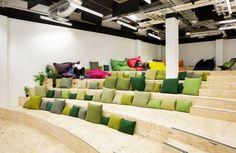 espace de travail en bois brut à l'aspect amphithéâtre, et coussins décoratifs en vert et gris taupe