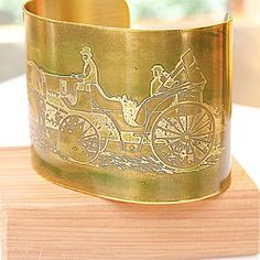 A beautiful horse and carriage design was etched onto brass, creating this lovely bangle.  It's painted in the softest shade of moss green.  $40.00