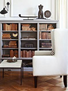 A bookcase boasts dark interior panels so that the weathered brown books pop against its deep gray tones - Traditional Home® / Design: Michael Del Piero Nook, Low Bookshelves, Bookcase Organization, Grey Shelves, Book Shelves, Bookcase Styling, Interior Exterior, Exterior Colors, Ikea