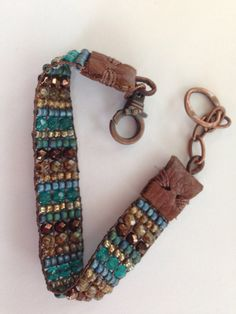 Lakes and woods. Blues,teals,woodsy browns and gold. Hand loomed beaded bracelet. Leather end tabs, copper adjustable chain and clasp
