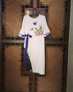 A sweet yet trendy outfit in white linen, sporting a cute hand painted motif. The asymmetrical hemline and smart bell sleeves add a touch of trendy elegance. Kurti Embroidery Design, Embroidery Fashion, Embroidery Dress, Ribbon Embroidery, Kurta Designs, Blouse Designs, Navratri Dress, Lace Dress With Sleeves, Bell Sleeves