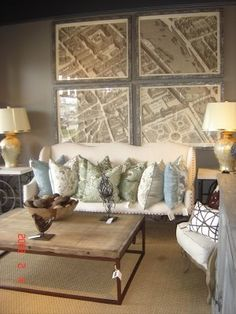 Gray walls, maps, light colored furniture with pops of color from the pillows.