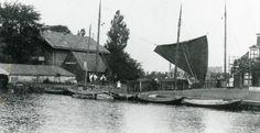 Aan de wal een paar boatsjes en een installatie met visbeunen. Links het Koetshuis met links vooraan een boothuis. Achter het zeil verscholen kunt u de contouren zien van de zuivelfabriek. Uitgave Tj. de Vries