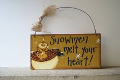 Rustic snowman sign. Hand painted wood snowman sign. The front of this sign has been painted a mustard yellow flecked with cream, edges have been distressed. A rustic snowman wearing mittens, a scarf and winter coat has been hand painted on along with the saying Snowmen melt your heart!.