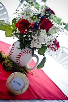Centerpieces in large Baseball Mugs sat on moss and a red napkin. Red Sox Baseball ornaments were attached to picks and added to each arrangement. We had a Red Sox Baseball Lottery Ticket taped under one chair at each table. The person to the left of whoever had the lottery ticket won the flowers and the person to the right got the personalized bottle of wine to take home. Some people traded!