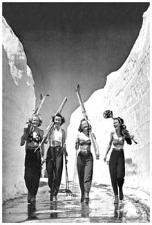 So California girls ALWAYS had this much fun! This features a vintage black-and-white image that combines classic style, massive snow, and young ladies in bikinis, to give you a bright, optimistic look at the ski life. Taken on volcanic Mt. Lassen in Northern California on July 4, 1942, on a road that was cleared for the first time all year.