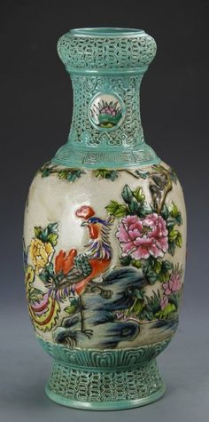 Chinese Famille Rose Vase decorated with a turquoise glaze at the neck and foot, painted with a colorful scene of a rooster in a garden setting. Height 17 in.