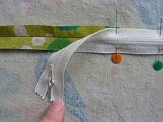 With the wrong side of the fabric facing up, place the zipper right-side down, aligning the zipper teeth directly over the seam. Pin it in place.