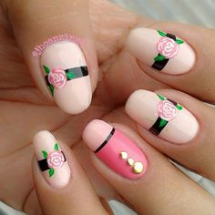 This is a very cute looking baby pink nail art design. A darker shade of pink polish is also used as well as black for the horizontal lines across the nails. Pink roses are painted on top with additional gold beads.