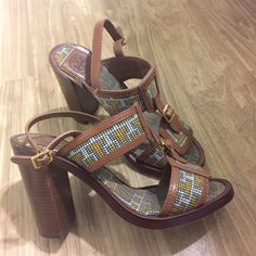 """Authentic Tory Burch block sandals. Authentic Tory Burch block sandal. Made in Brazil. Size 7M. Great condition. No Knicks or scratches except on the bottoms as pictures from gentle normal use. Leather is a tan color and the """"T's"""" are yellow with green outline. Perfect block sandals for spring/summer and won't sink in grass. Heel size is about 4"""". For any other questions feel free to ask. Tory Burch Shoes Sandals"""