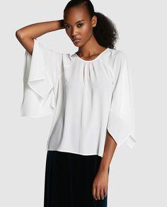 Blusa blanca y amplia, tipo kimono, con manga larga y escote redondo. Con detalle de pliegues.