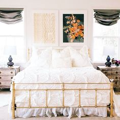 Master bedroom. White comforter. White pillows. Two large pictures above bed. Wooden night stands. Window coverings. Roman shaded. Golden bed frame.