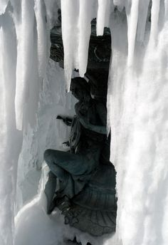 a fountain with frozen water creating an ice window