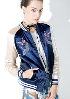 Lucky Crane Bomber Jacket cuz yer always givin' us hope, bb. This gorgeous bomber jacket features a sleek 'N satiny navy blue construction, sleek fit, contrasting cream colored sleeves with striped banded cuffs, intricate traditional floral embroidery with crane imagery across the chest and back, side pockets, and zip front closure.