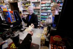 : Cashiers Kathy Robinson, left, and Ethel Kroska, right, both of Merrimack, N.H., sell a lottery ticket at Reeds Ferry Market convenience store.<br />