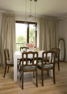 dining room with antique chairs and mirror in antique carved frame, white table, oak floor