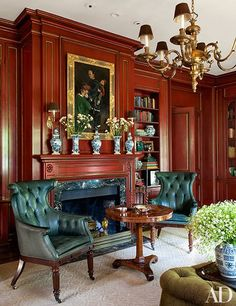 The library paneling has been painted a classic Chinese red with gilt detailing; the 19th-century-style wing chairs are upholstered in a leather by Rose Tarlow Melrose House.