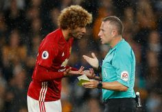 Marouane Fellaini is booked by referee Jonathan Moss