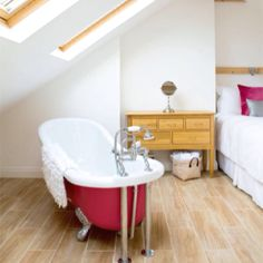 bath in bedroom under angled ceiling with skylights
