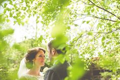 Bride & Groom through lime green leaves in May. Ripponden, West Yorkshire.