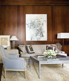 Clean-lined furniture, modern lamps and a painting by artist Jimmy O'Neal provide contemporary counterpoints to the study's traditional paneled walls. Brown chose a Rogers amp; Goffigon blue-gray plaid fabric for the sofa, a nod to the husband's English roots. The artwork on the side table is by Tom Swanston.