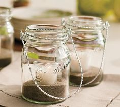 Hanging mason jars with sand and tealights.