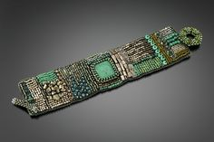 Silver and Turquoise Embroidered Cuff by Julie Powell. Glass beads from Czech Republic and Japan, embroidered one bead at a time into a fabric by hand. Accented with Tibetan turquoise, pyrite, London blue and smoky quartz. Backed with Ultrasuede for durability and softness. Hand woven toggle closure. Limited edition of 25.