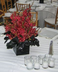 This is a cube vase floral arrangement that features red mokara orchids with accents of curly willow branches. See our entire selection at www.starflor.com.  To purchase any of our floral selections, as gifts or décor, please call us at 800.520.8999 or visit our e-commerce portal at www.Starbrightnyc.com. This composition of flowers is generally available for same day delivery in New York City (NYC). SQ219