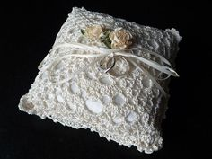 I made this ring pillow for my son's wedding. The crochet square is sewn on to a satin pillow, and it is decorated with a fabric flower and some ribbon.