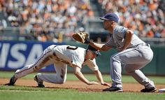 San Francisco Giants' Gary Brown, left, dives back to first base on a pick off attempt as San Diego Padres first baseman Jake Goebbert, right, waits for the throw in the first inning of their baseball game Saturday, Sept. 27, 2014, in San Francisco. (AP Photo/Eric Risberg)