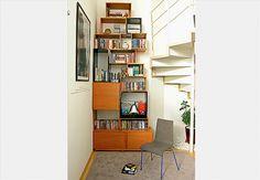 O designer Estevão Toledo aproveitou o pé-direito duplo para criar esta estante estreita e alta, ao lado da escada caracol. Para dar movimento ao móvel, montou-o com nichos de diferentes tamanhos e formas