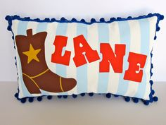 Baby pillow in baby blue stripes with cowboy boot accent. Personalized with name.