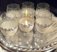 This glitter candle holder set includes 6 tealight/votive holders with flower bling wrap (no actual stones) and a button gem (2-small holes inset but only noticeable with close inspection). Height is 4 1/2 approx. And comes with 6 white tealight candles. (Bling ribbon or bling flower wrap can be added to the tealight candles upon reques for an extra charge). Add a black glove, silver charger, a string of pearls or feathers to make the sophisticated 1920s style come to life for your event…