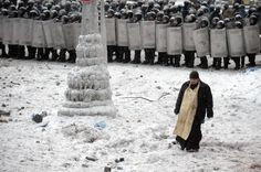 A Ukrainian priest walks in no-man's land as riot police look on.