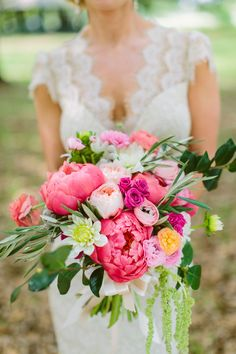 Pink and blush garden bouquet using peonies, garden roses, ranunculus, spray roses, magnolia foliage, hanging amaranthus, and olive branches