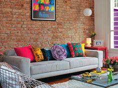 Sofá cinza trás suavidade ao ambiente colorido