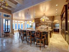Bright and open, the gourmet kitchen includes a spacious prep island, ample bar seating and ornately carved details on the barstools, cabinets and island.