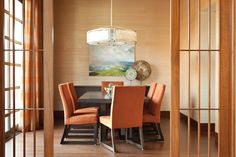 The dining room walls are covered in a Phillip Jeffries grass cloth. Over the table, which is surrounded by a sextet of orange chairs, hangs a Corbett Lighting fixture made from metal and Japanese paper. The oil painting is by Craig Mooney Decor, Orange Dining Room, Contemporary Dining Room, Luxe Interiors, Lamp Decor, Contemporary Interior, Orange Decor, Interior Design, Dining