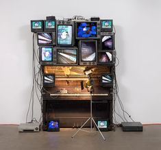Nam June Paik|Untitled - 1993. Player piano, 15 televisions, two cameras, two laser disc players, one electric light and light bulb, and wires, overall approx. 8′ 4″ x 8′ 9″ x 48″ (254 x 266.7 x 121.9 cm), including laser disc player and lamp. The Museum of Modern Art, New York. Bernhill Fund, Gerald S. Elliot Fund, gift of Margot Paul Ernst, and purchase. © 2013 Estate of Nam June Paik