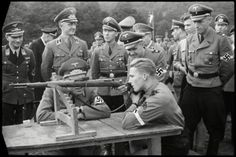Gauleiter Hoffmann and HJ-Gebietsführer Hugo Bald obeserve a shooting excercise from a member of the Hitler Youth (HJ).