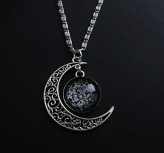 This moon necklace looks like the starry night sky was captured inside the pendant