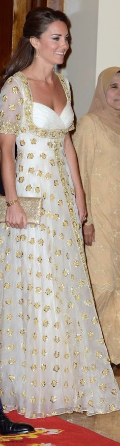 The Duchess wore a bespoke long cream gown by Alexander McQueen. The stunning gown features an overleaf of sheer material with the Malaysian hibiscus flowers embroidered in gold. The dress has a sweetheart neckline, a full skirt and fitted bodice