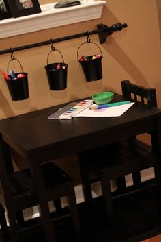 Buckets on a curtain rod. Great for classroom or office.  Would love to create a designated place for kids to sit down and do crafts like this...