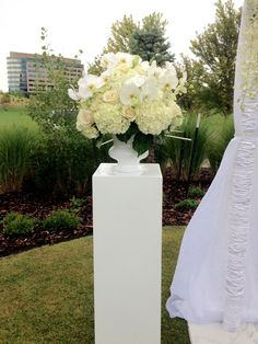 white modern pedestals that will be used with compact, lush florals in the wedding flowers and hues at the entrance to the aisle, and then later in the center collage of the reception table.