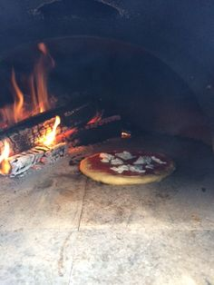 pizza coming out of a wood fired portable oven